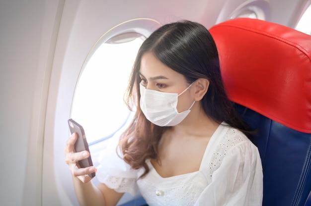 Una mujer joven con mascarilla está usando un teléfono inteligente a bordo, nuevo viaje normal después del concepto de pandemia covid-19