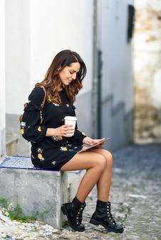 Mujer joven de mediana edad con tableta digital al aire libre