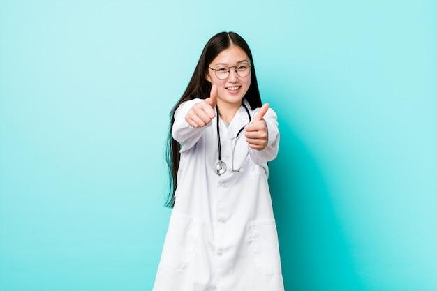 Mujer joven médico chino con pulgares arriba, aplausos sobre algo, apoyo y respeto.