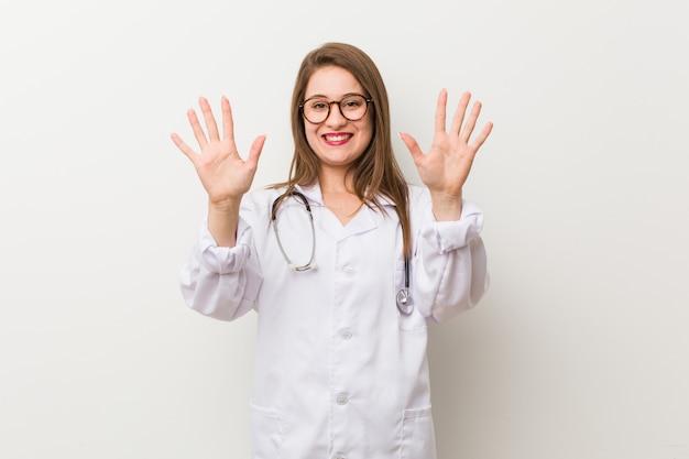 Mujer joven médico contra una pared blanca que muestra el número diez con las manos.