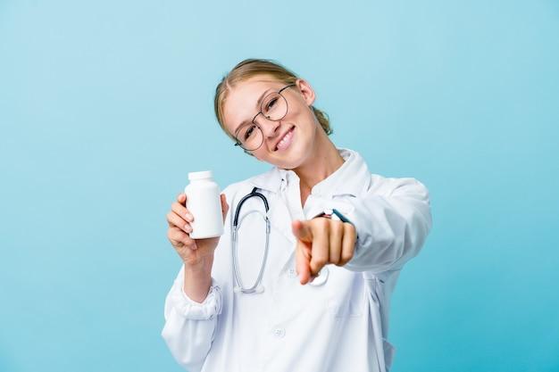 Mujer joven médico ruso sosteniendo la botella de píldoras en sonrisas alegres azules apuntando al frente.
