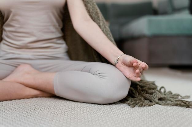 Mujer joven meditando en casa cerrar