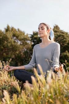 Mujer joven meditando en la naturaleza