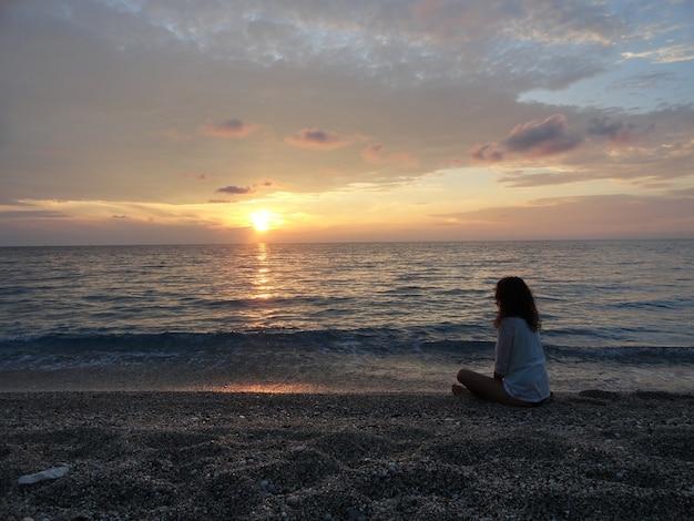 Mujer joven meditando en una playa griega al atardecer