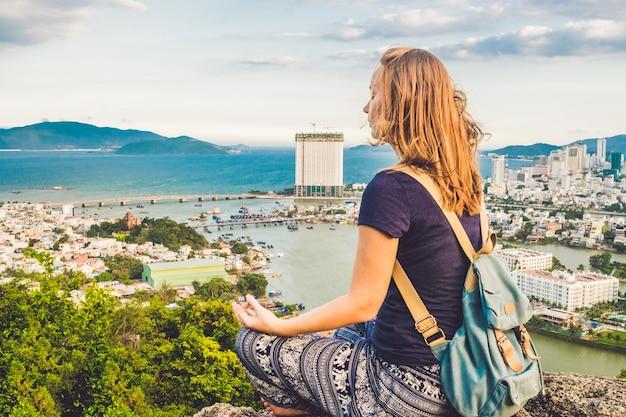 Mujer joven meditando sobre el paisaje de la ciudad antigua