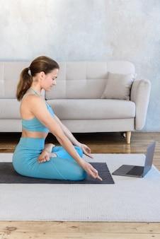 Mujer joven meditando yoga mientras ve la lección en video en la computadora portátil en casa