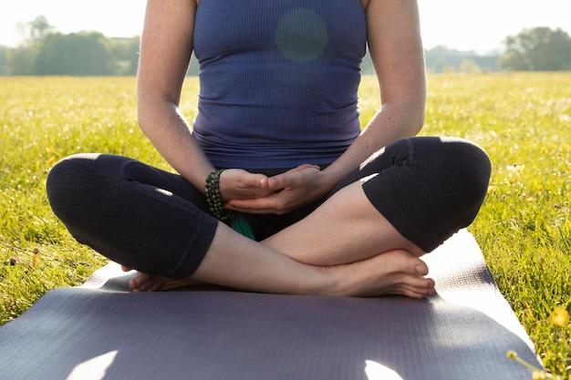 Mujer joven, meditar, aire libre, en, estera de yoga