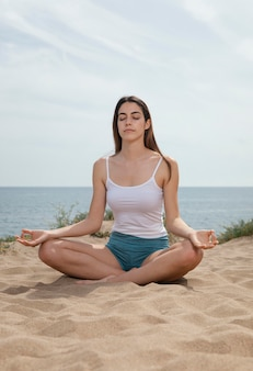 Mujer joven, meditar, en, arena