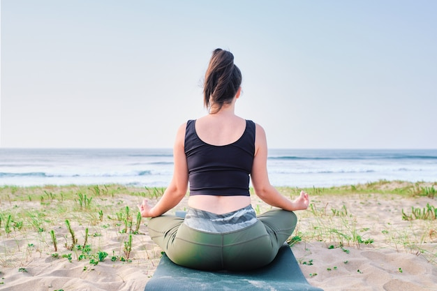 Mujer joven, meditar, en la playa
