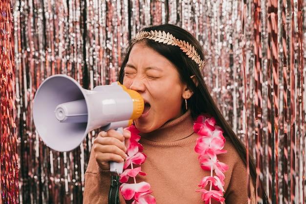 Mujer joven con megáfono en fiesta de carnaval
