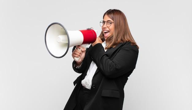 Mujer joven con un megáfono que se siente feliz, positiva y exitosa, motivada al enfrentar un desafío o celebrar buenos resultados.