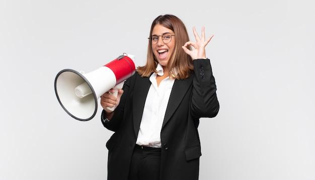 Mujer joven con un megáfono que se siente feliz, relajada y satisfecha, mostrando aprobación con gesto bien, sonriendo
