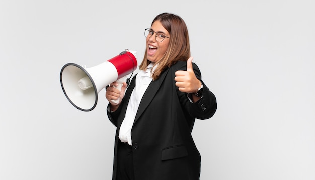 Mujer joven con un megáfono que se siente orgullosa, despreocupada, segura y feliz, sonriendo positivamente con los pulgares hacia arriba