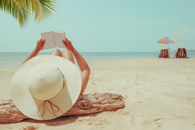 La mujer joven en la mentira del sombrero de paja toma el sol en una playa tropical