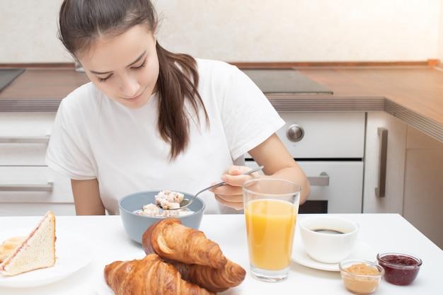 Mujer joven en la mesa en la cocina comiendo granola