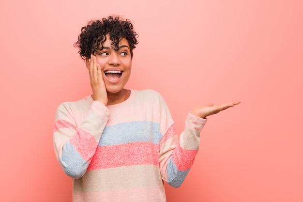 La mujer joven mezclada del adolescente del afroamericano sostiene la copia en una palma, guarda la mejilla de la mano. sorprendido y encantado.