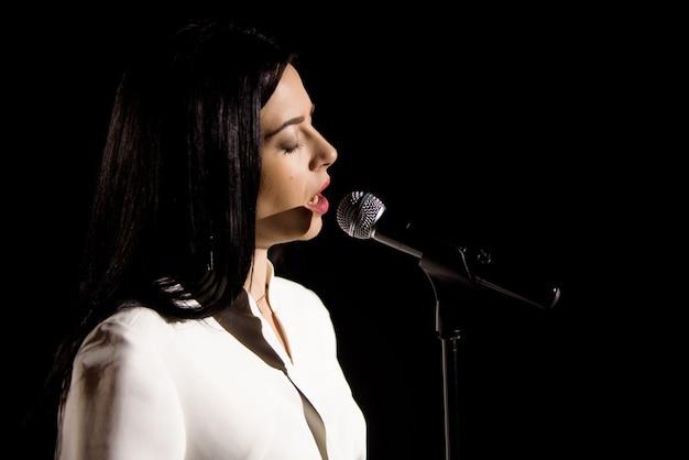Mujer joven con micrófono y luces blancas en un concierto