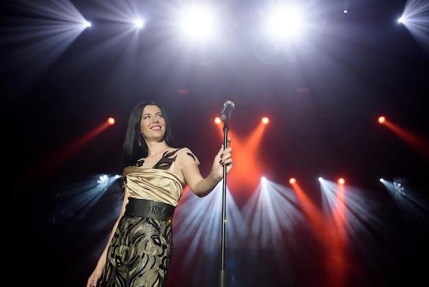 Mujer joven con micrófono en mano en evento de entretenimiento.