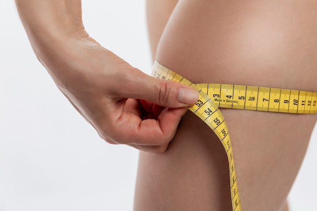 Mujer joven mide el volumen del muslo. cuidando la figura. fondo blanco. vertical.
