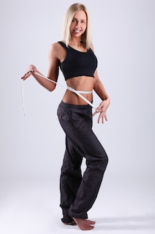 Mujer joven midiendo su cintura con cinta métrica