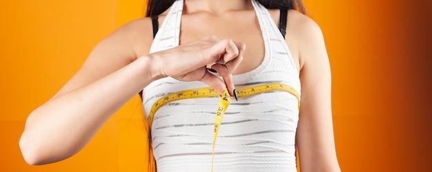 Mujer joven midiendo sus senos con una cinta