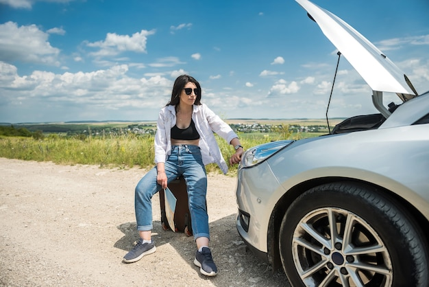 Mujer joven mira debajo del capó del motor como motor de coches rotos. rotura de coche en carretera. vacaciones detenidas