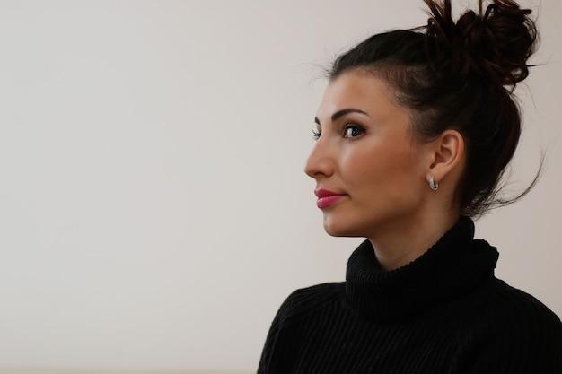 Una mujer joven mira por la ventana de un apartamento nuevo