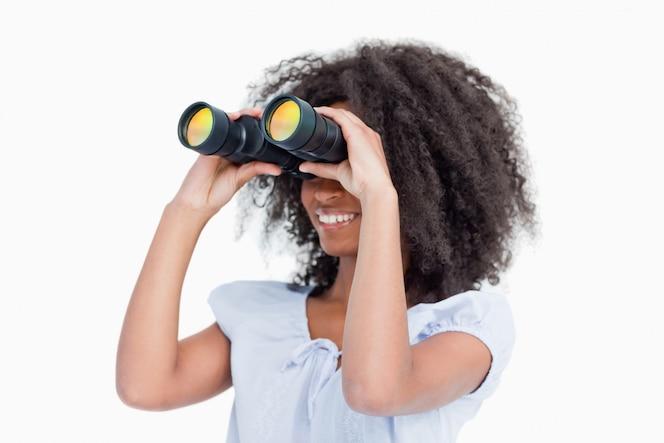Mujer joven mirando a un lado a través de binoculares