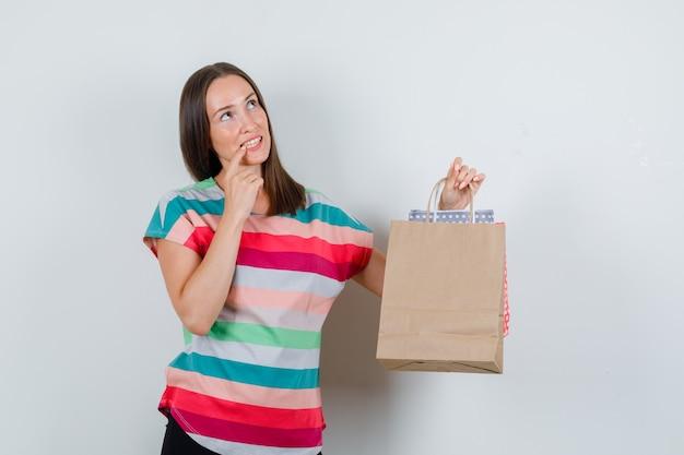 Mujer joven mirando hacia arriba con bolsas de papel en camiseta, pantalón y mirando pensativo. vista frontal.