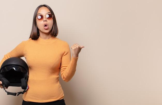 Mujer joven mirando asombrada con incredulidad, señalando un objeto en el costado y diciendo wow, increíble