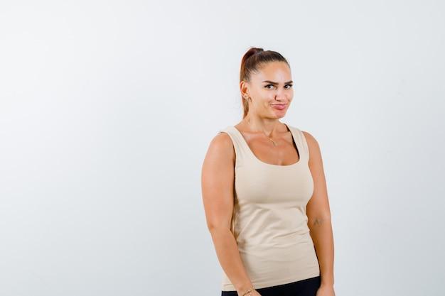 Mujer joven mirando a la cámara en la camiseta sin mangas beige y mirando linda, vista frontal.