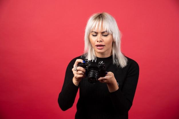 Mujer joven mirando una cámara sobre un fondo rojo. foto de alta calidad