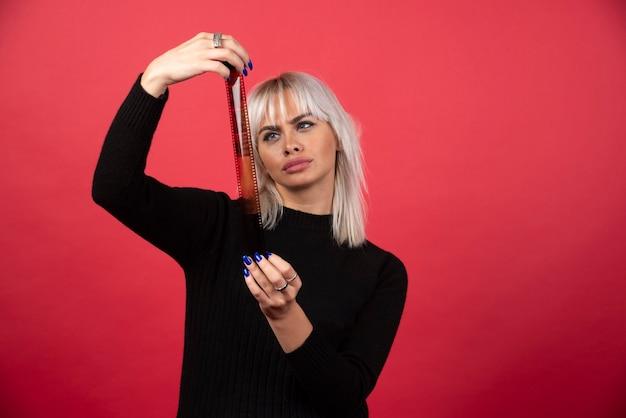 Mujer joven mirando una cinta fotográfica sobre un fondo rojo. foto de alta calidad