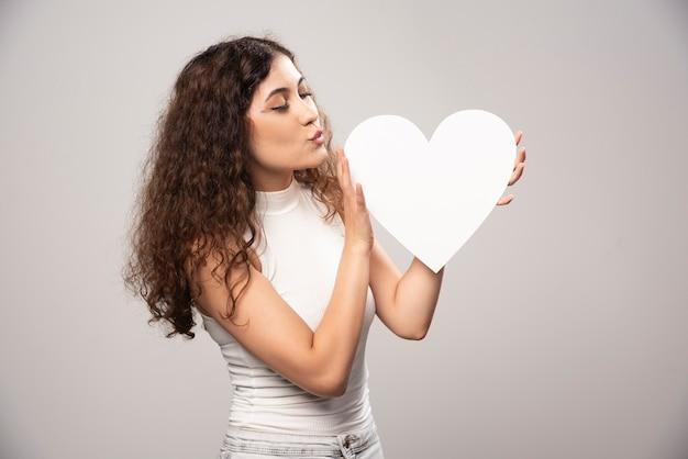 Mujer joven mirando corazón de papel hecho a mano blanco. foto de alta calidad
