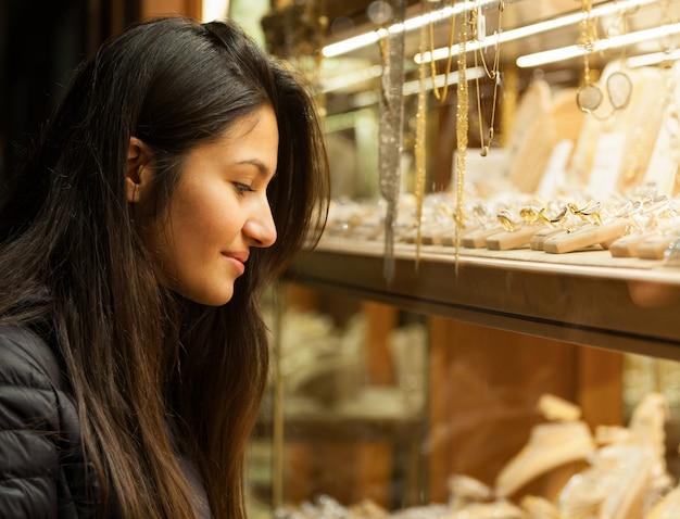 Mujer joven mirando el escaparate de una joyería al aire libre
