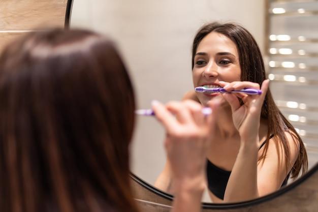 Mujer joven mirando en el espejo mientras se cepilla los dientes, higiene dental