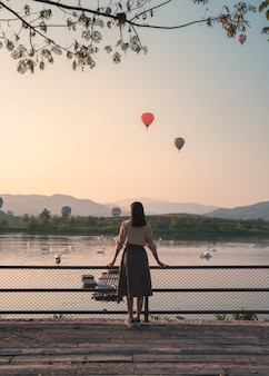 Mujer joven mirando un globo de aire caliente en el patio de madera