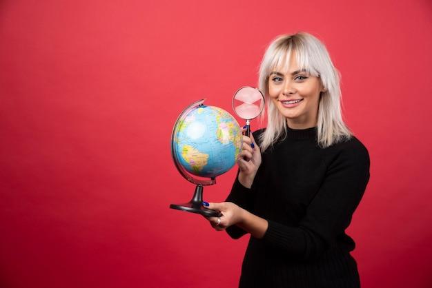 Mujer joven mirando un globo con lupa sobre un fondo rojo.