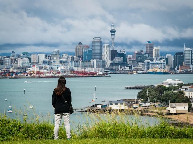 Mujer joven mirando el horizonte de la ciudad de auckland