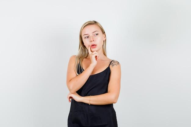 Mujer joven mirando a un lado con el dedo cerca de la boca en camiseta negra y mirando con cuidado.