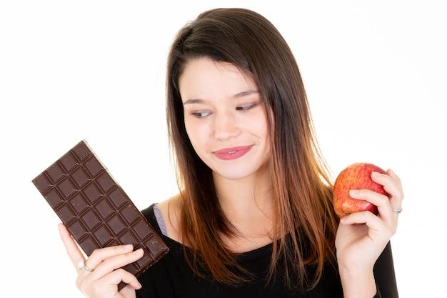 Mujer joven mirando manzana fresca mientras se come barra de chocolate