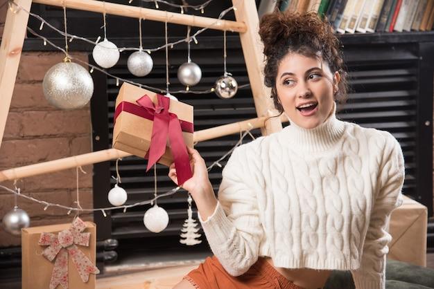 Una mujer joven mirando a otro lado y sosteniendo una caja de regalo con lazo