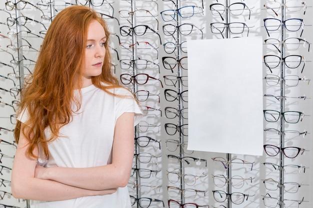Mujer joven mirando papel blanco en blanco en la tienda de óptica
