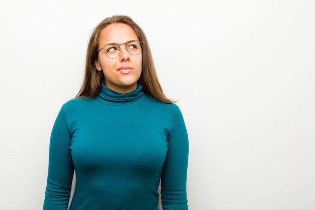 Mujer joven mirando perplejo y confundido, preguntándose o tratando de resolver un problema o pensando contra el fondo blanco.