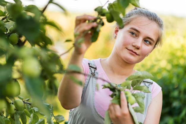 Mujer joven mirando ramas de los árboles