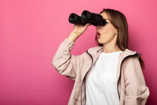 Mujer joven mirando con sorpresa a través de binoculares