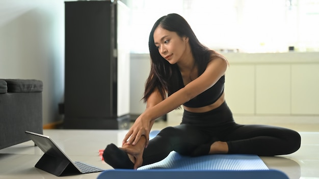 Una mujer joven está mirando a una tableta mientras hace un ejercicio en la colchoneta de ejercicios