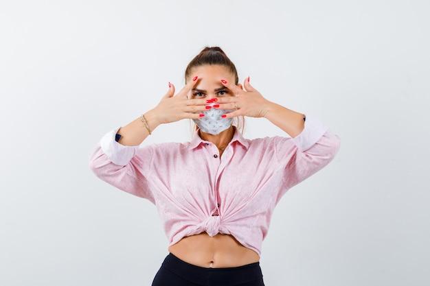 Mujer joven mirando a través de los dedos en camisa, pantalón, máscara médica y luciendo linda, vista frontal.