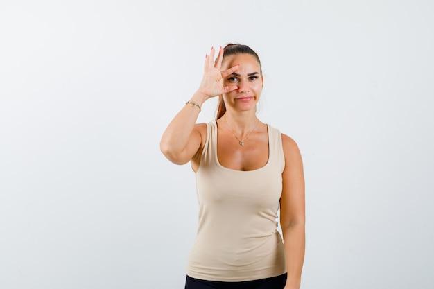 Mujer joven mirando a través de los dedos en la camiseta sin mangas de color beige y mirando bastante