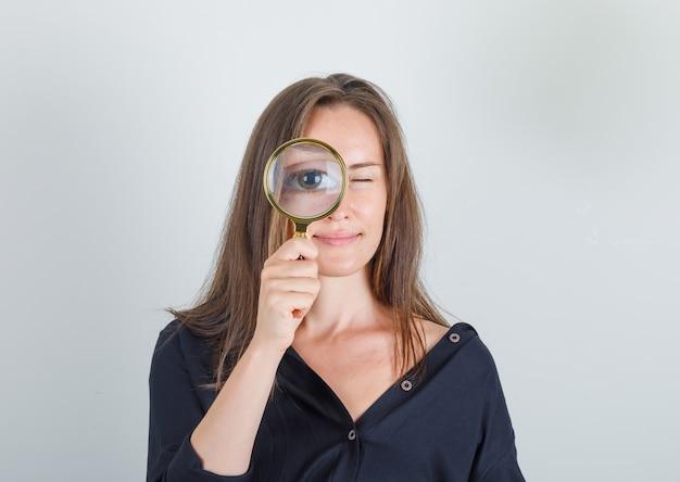 Mujer joven mirando a través de la lupa en camisa negra